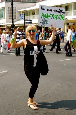 """Foto einer lachenden Demoteilnehmerin mit einem Schild mit der Aufschrift """"Für eine vernünftige Hanfpolitik"""""""