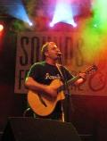 Foto von Götz Widmann mit Gitarre auf einer Bühne