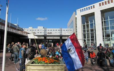 Foto der Versammlung zum 420 Smoke-Out vor Stadthalle und Rathaus in Amsterdam. Im Vordergrund eine niederländische Flagge mit Anonymous-Logo