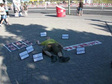"""Foto einer """"Leiche"""" mit Transpis und Schildern bei einer der Straßenaktionen"""