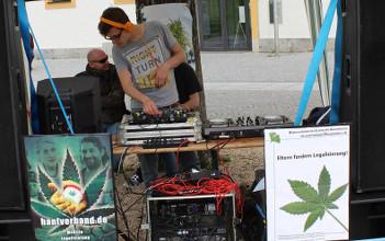Foto vom DJ am DJ-Pult neben Demoschildern